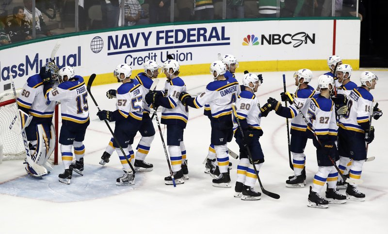 St. Louis Blues' Jordan Binnington (50) is congratulated by Robby Fabbri (15) and the rest of the team after their win against the Dallas Stars in Game 3 of an NHL second-round hockey playoff series in Dallas, Monday, April 29, 2019. (AP Photo/Tony Gutierrez)