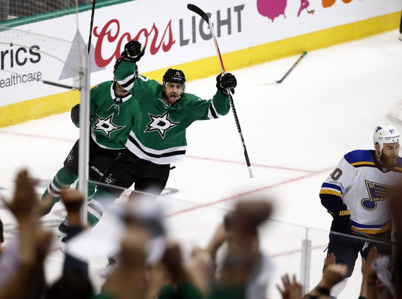 Fans, foreground, cheer as Dallas Stars center Andrew Cogliano (17) celebrates his goal in the third period of Game 3 of an NHL second-round hockey playoff series as St. Louis Blues' Ryan O'Reilly (90) skates away in Dallas, Monday, April 29, 2019. (AP Photo/Tony Gutierrez)