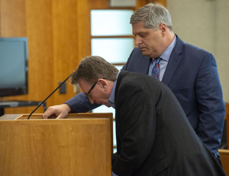 Sterling Van Wagenen, left, signs an agreement with his attorney, Steven Shapiro, as he pleads guilty during his initial appearance Tuesday, April 30, 2019, in American Fork, Utah. Van Wagenen, a Utah filmmaker who co-founded the Sundance Film Festival and produced an Oscar-winning movie in the mid-1980s has pleaded guilty to sexual abuse of a child. The 71-year-old Van Wagenen entered his plea during a court hearing in American Fork, Utah, south of Salt Lake City. (Rick Egan /The Salt Lake Tribune, via AP, Pool)