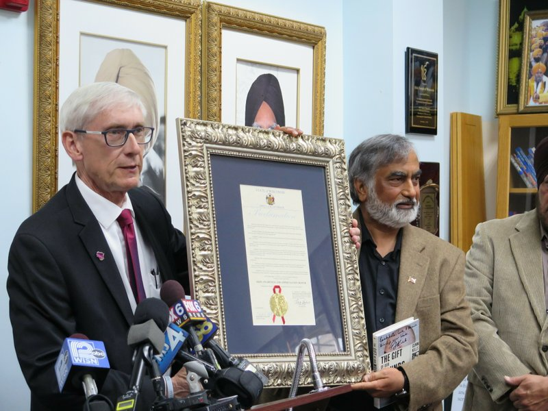 Wisconsin Gov. Tony Evers, left, presents a proclamation marking April as Sikh Awareness and Appreciation month, Tuesday, April 30, 2019, in Oak Creek, Wis. Standing alongside the governor is Masood Akhtar, who started a group called,