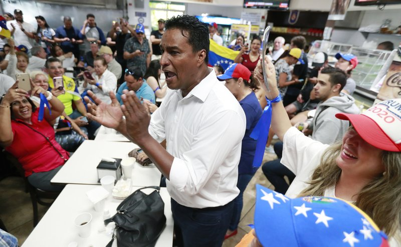 Venezuelan exile and former political prisoner Delson Guarte, the ex-mayor of Mario Briceño Iragorry Municipality, chants as he and others watch televised news from their country at the El Arepazo Doral Venezuelan restaurant, Tuesday, April 30, 2019, in Doral, Fla. Venezuelan opposition leader Juan Guaidó took to the streets with a small contingent of heavily armed troops early Tuesday in a bold and risky attempt to lead a military uprising and oust socialist leader Nicolas Maduro.  (AP Photo/Wilfredo Lee)