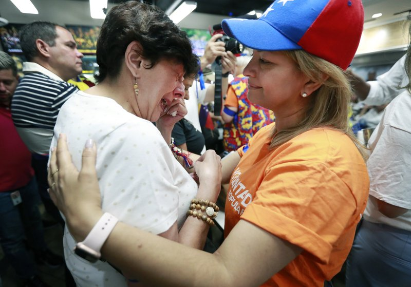 Rita Sanchez, right, comforts Miriam Abraham as they and other Venezuelans watch televised news from their country at the El Arepazo Doral Venezuelan restaurant, Tuesday, April 30, 2019, in Doral, Fla. Venezuelan opposition leader Juan Guaidó took to the streets with a small contingent of heavily armed troops early Tuesday in a bold and risky attempt to lead a military uprising and oust socialist leader Nicolas Maduro.  (AP Photo/Wilfredo Lee)