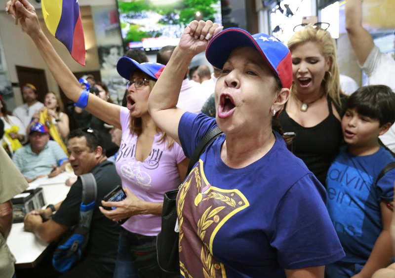 Arelys Lopez, foreground, leads a cheer as Venezuelans chant while watching televised news from their country at the El Arepazo Doral Venezuelan restaurant, Tuesday, April 30, 2019, in Doral, Fla. Venezuelan opposition leader Juan Guaidó took to the streets with a small contingent of heavily armed troops early Tuesday in a bold and risky attempt to lead a military uprising and oust socialist leader Nicolas Maduro. (AP Photo/Wilfredo Lee)