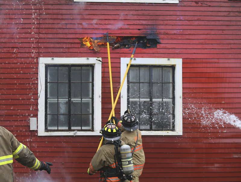 North Bennington firefighters break through the exterior as they battle a blaze at