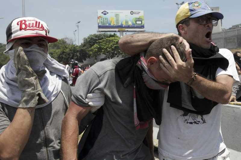 An injured man is aided by fellow anti-government protesters during clashes with security forces loyal to President Nicolas Maduro, during an attempted military uprising in Caracas, Venezuela, Tuesday, April 30, 2019. Venezuelan opposition leader Juan Guaidó and jailed opposition leader Leopoldo Lopez took to the streets with a small contingent of armed troops early Tuesday in a call for the military to rise up and oust Maduro. (AP Photo/Boris Vergara)