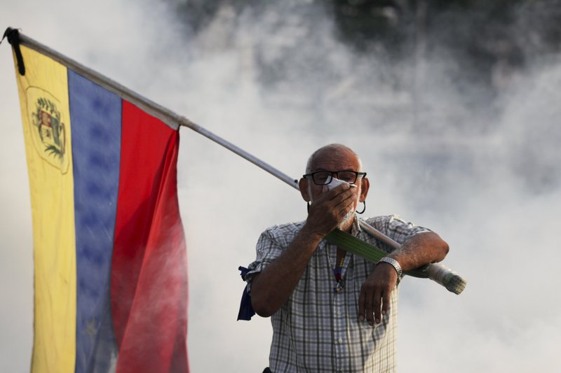 An opponent to Venezuelan President Nicolas Maduro carrying a Venezuelan flag covers his face amid tear gas fired by soldiers loyal to Maduro during an attempted military uprising to oust Maduro in Caracas, Venezuela, Tuesday, April 30, 2019. Venezuelan opposition leader Juan Guaidó and jailed opposition leader Leopoldo Lopez took to the streets with a small contingent of armed troops early Tuesday in a call for the military to rise up and oust Maduro. (AP Photo/Boris Vergara)