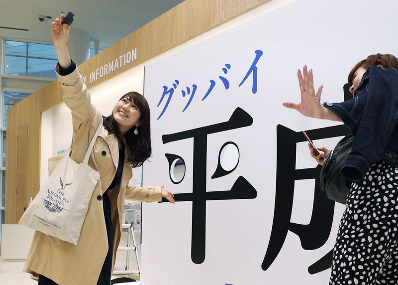 Visitors take a selfie with a panel with