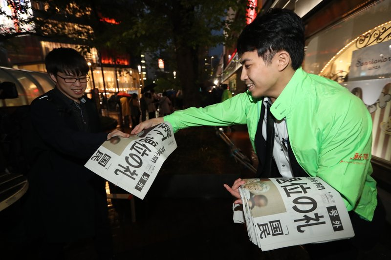 A Yomiuri newspaper worker hands a copy of the extra edition reporting Emperor Akihito's abdication in Tokyo Tuesday, April 30, 2019. Japan's Emperor Akihito announced that he is abdicating as of Tuesday at a ceremony, in his final official address to his people. The headline, partly seen, reads