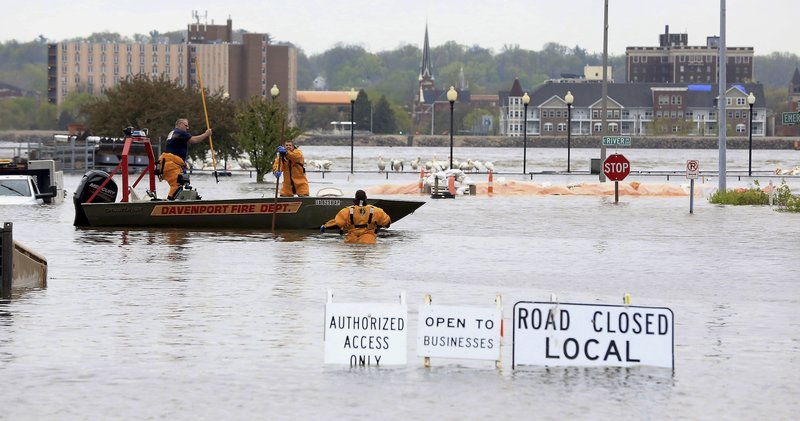 Davenport firefighters search the area after the floodwall failed at River Drive and Pershing Avenue sending Mississippi River floodwater into several blocks of downtown Davenport, Iowa Tuesday, April 30, 2019. (Kevin E. Schmidt/Quad City Times via AP)