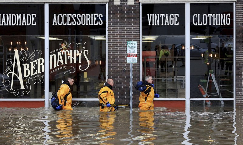 Davenport firefighters move building to building checking for people trapped after the floodwall failed at River Drive and Pershing Avenue sending Mississippi River floodwater into several blocks of downtown Davenport, Iowa Tuesday, April 30, 2019. (Kevin E. Schmidt/Quad City Times via AP)