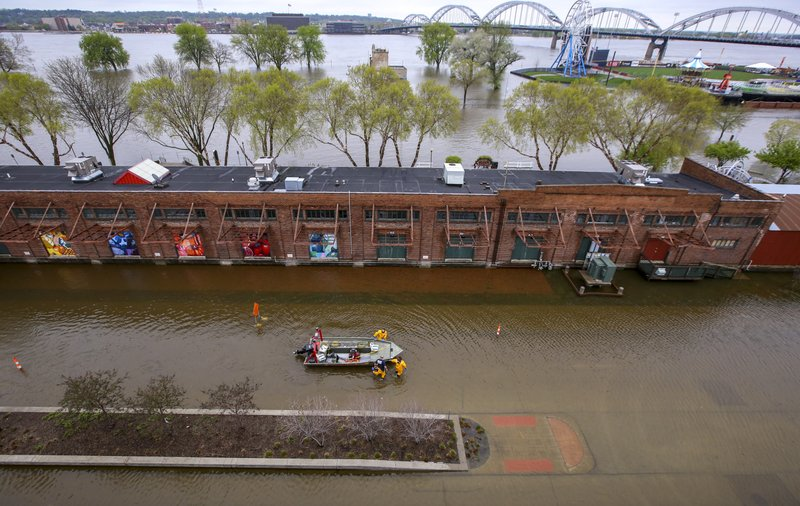 Davenport firefighters walk a rescue boat down West River Drive along the freight house in Davenport, Tuesday, April 30, 2019. (Andy Abeyta/Quad City Times via AP)