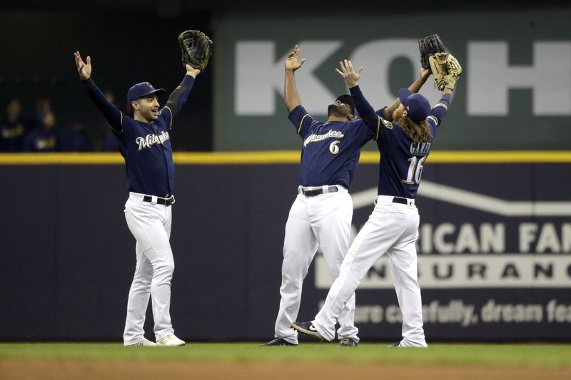 Milwaukee Brewers' Lorenzo Cain (6), Ryan Braun, and Ben Gamel (16) celebrate the team's 4-3 win in a baseball game against the Colorado Rockies on Tuesday, April 30, 2019, in Milwaukee. (AP Photo/Aaron Gash)