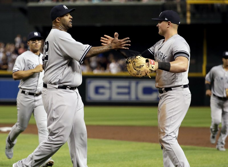 New York Yankees starting pitcher CC Sabathia, left, celebrates with first baseman Luke Voit after throwing his 3,000th career strikeout, during the second inning of the team's baseball game against the Arizona Diamondbacks, Tuesday, April 30, 2019, in Phoenix. (AP Photo/Matt York)