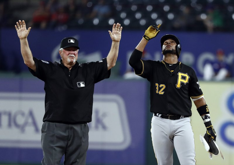 Second base umpire Dana DeMuth signals time as Pittsburgh Pirates' Elias Diaz (32) celebrates his double to left in the fourth inning of a baseball game against the Texas Rangers in Arlington, Texas, Tuesday, April 30, 2019. (AP Photo/Tony Gutierrez)