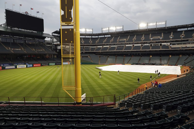 Members of the Pittsburgh Pirates warm up in the outfield of a tarp-covered Globe Life Park field as light rain showers pass through before a baseball game against the Texas Rangers in Arlington, Texas, Tuesday, April 30, 2019. (AP Photo/Tony Gutierrez)