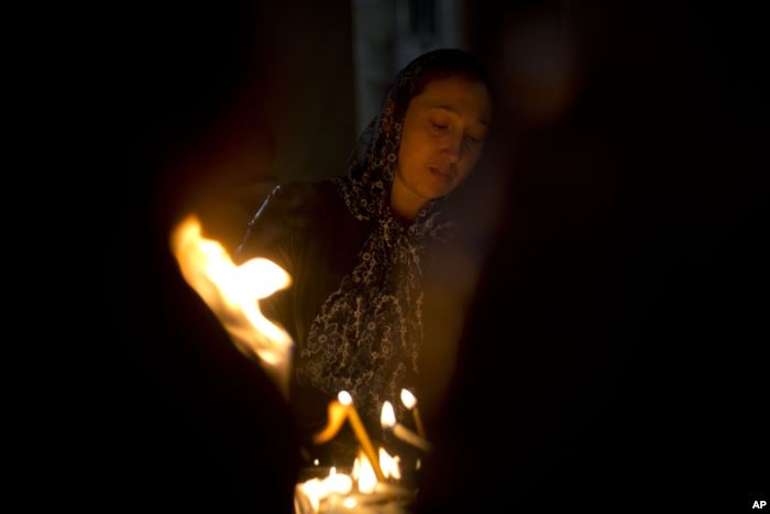 A Christian woman prays in the Church of the Holy Sepulchre, traditionally be