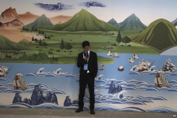 A man stands near a mural depicting the ancient Silk Road during the Second B