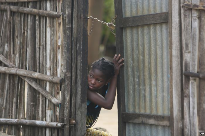A young girl takes a look outside a gate near a site where two houses were cr