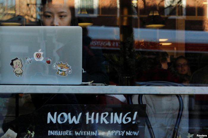 """FILE - A """"Now Hiring"""" sign sits in the window of a bakery-cafe in C"""