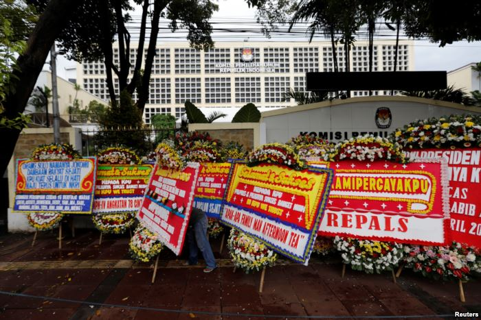 FILE - A worker arranges flower wreaths and congratulatory boards from people
