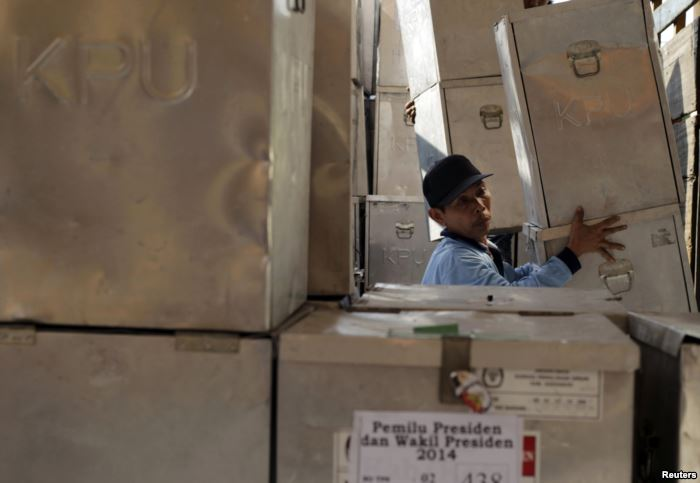 FILE - A worker unloads ballot boxes for the upcoming Indonesian presidential