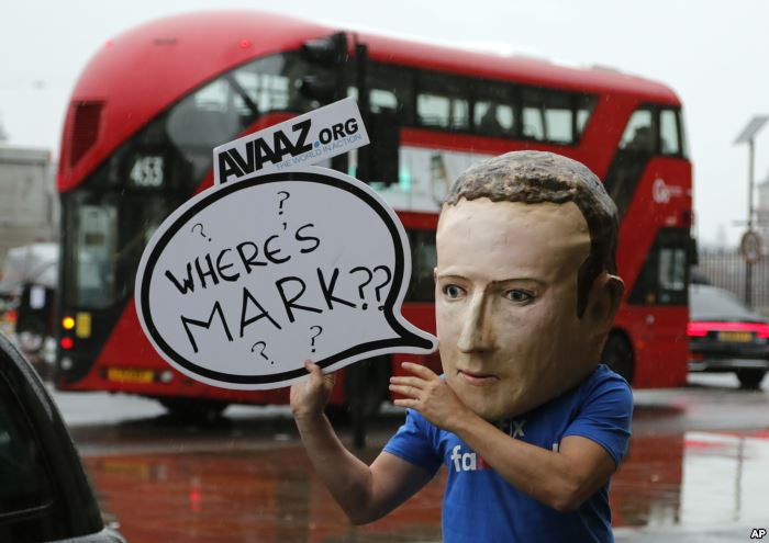 FILE - An activist wearing a Facebook CEO Mark Zuckerberg mask stands outside