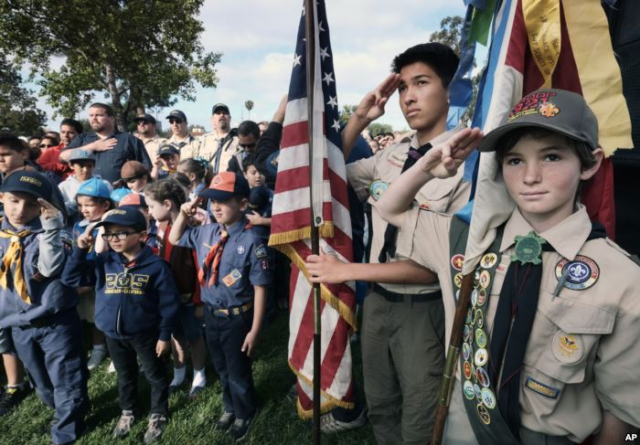 FILE - Boy Scouts and Cub Scouts salute the flag during ceremonies at the Los