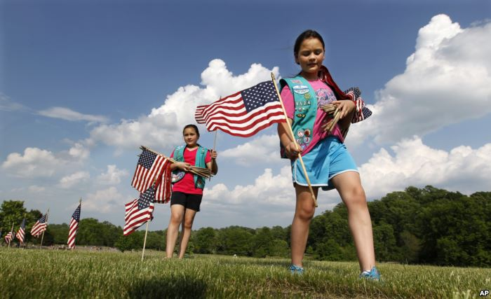 FILE - Girl Scouts place flags on veterans' graves at Brig. Gen. William