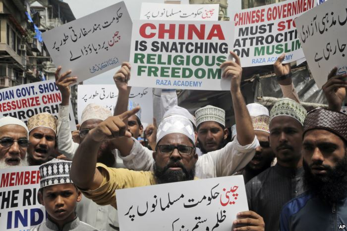 FILE - Indian Muslims shout slogans during a protest against the Chinese gove