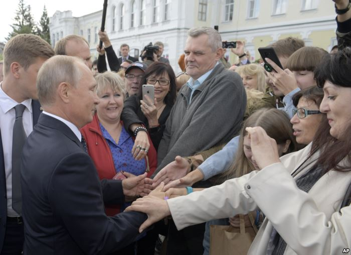 FILE - Russian President Vladimir Putin, left, greets local citizens in Omsk,