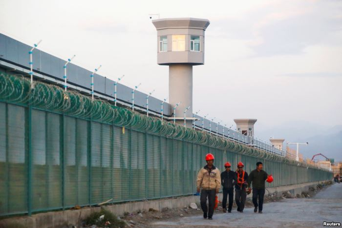 FILE - Workers walk by the perimeter fence of what is officially known as a v