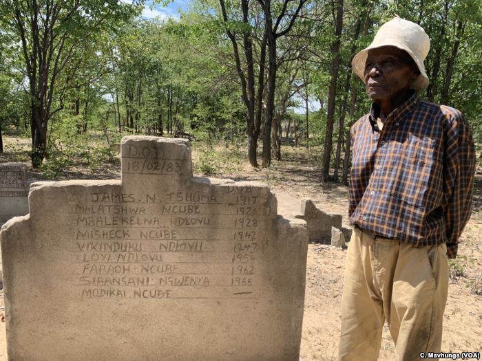Melwa Ngwenya stands in front of one of the shallow graves of victims of Zimb