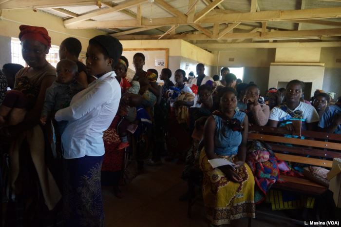 Mothers queue to have their children vaccinated against malaria at Likuni Com