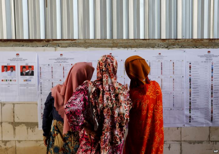 People look at voting information at a polling station during elections in Bo