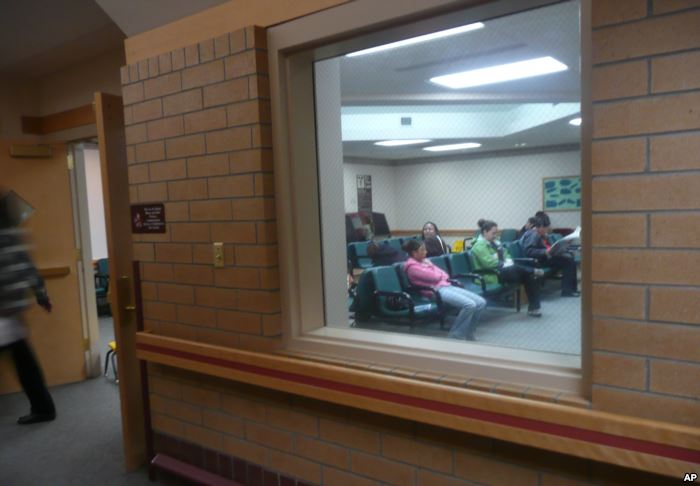 People sit in the waiting room of the Indian Health Service clinic in Crow Ag