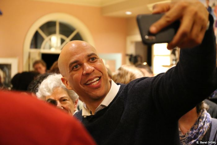 Senator Cory Booker of New Jersey takes selfies with voters at a New Hampshir