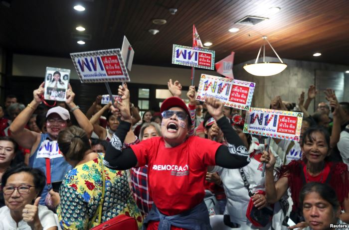 Supporters of Pheu Thai Party react after unofficial results, during the gene