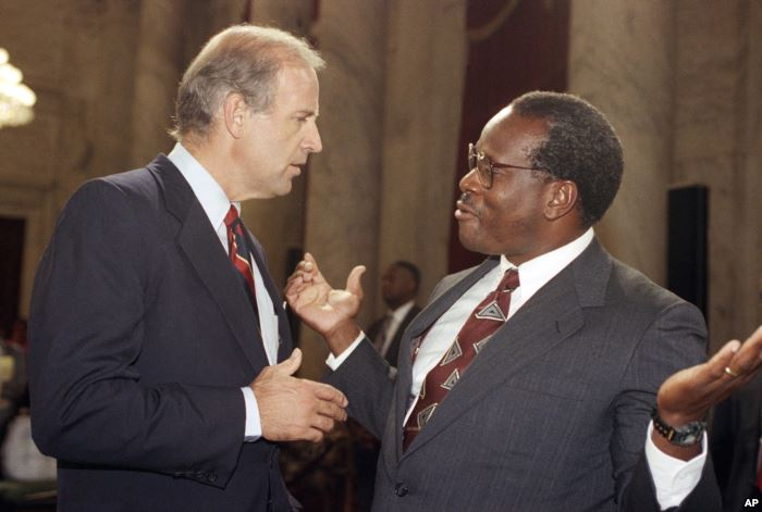 Supreme Court Justice Clarence Thomas gestures while talking with Sen. Joseph