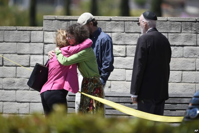 Synagogue members console one another outside of the Chabad of Poway Synagogu