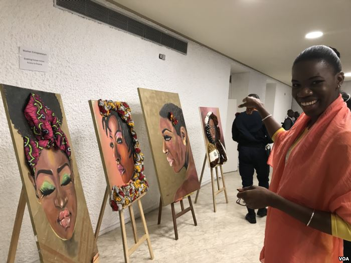 Tatou Dembele, a painter and owner of a food marketing company, points to her