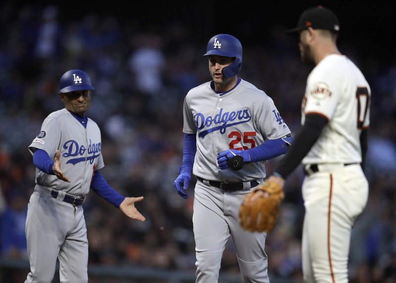 Los Angeles Dodgers third base coach Dino Ebel, left, reacts as David Freese (25) runs the bases after hitting a three run home run off San Francisco Giants' Drew Pomeranz, right, in the fourth inning of a baseball game Tuesday, April 30, 2019, in San Francisco. (AP Photo/Ben Margot)