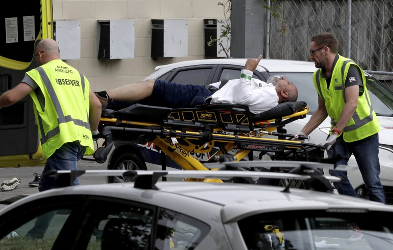 FILE - In this March 15, 2019, file photo, ambulance staff take a man from outside a mosque in central Christchurch, New Zealand. New Zealand's major media organizations pledged Wednesday, May 1, 2019, not to promote white supremacist ideology when covering the trial of the man charged with killing 50 people at two mosques.(AP Photo/Mark Baker, File)