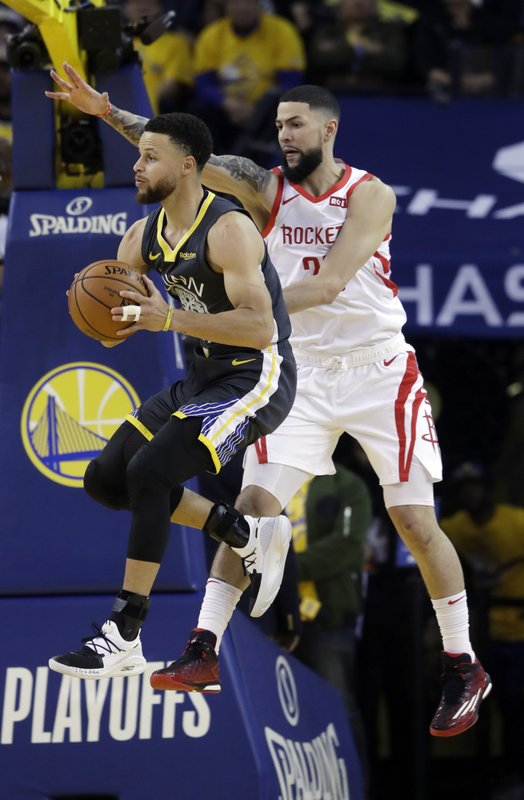 Golden State Warriors' Stephen Curry, left, is defended by Houston Rockets' Austin Rivers during the first half of Game 2 of a second-round NBA basketball playoff series in Oakland, Calif., Tuesday, April 30, 2019. (AP Photo/Jeff Chiu)