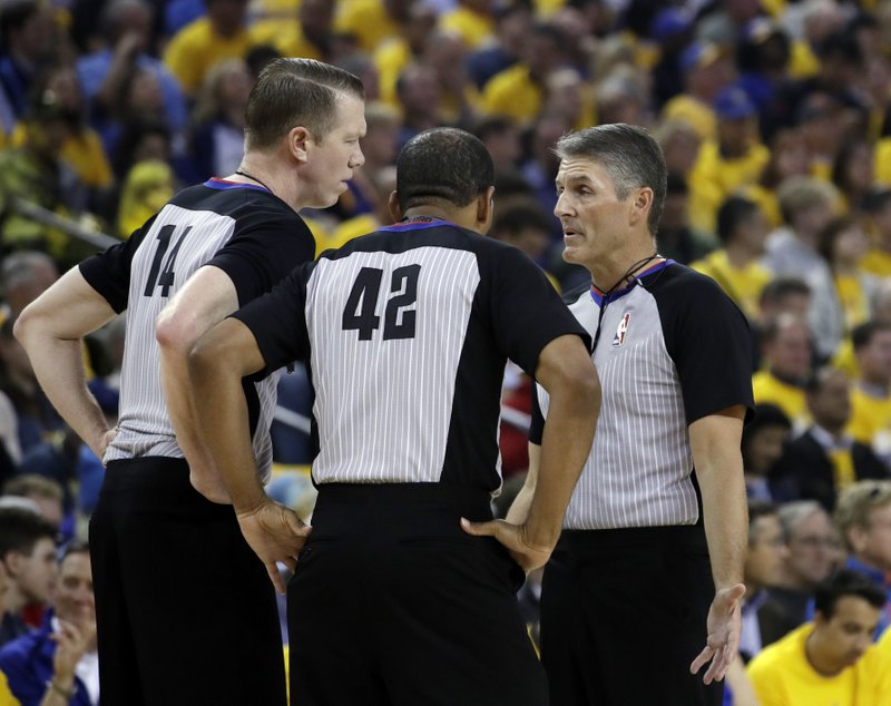 Referees huddle during the first half of Game 2 of a second-round NBA basketball playoff series between the Golden State Warriors and the Houston Rockets in Oakland, Calif., Tuesday, April 30, 2019. (AP Photo/Jeff Chiu)