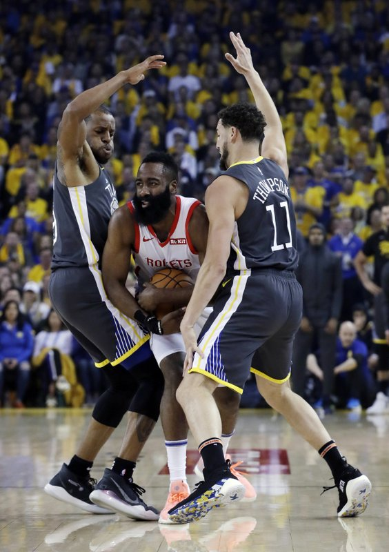 Houston Rockets' James Harden, center, is defended by Golden State Warriors' Andre Iguodala, left, and Klay Thompson during the first half of Game 2 of a second-round NBA basketball playoff series in Oakland, Calif., Tuesday, April 30, 2019. (AP Photo/Jeff Chiu)
