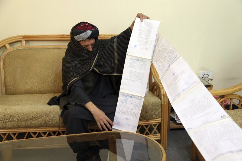 In this Sunday, April 28, 2019, photo, Aman, a former Taliban fighter from northern Kunduz province, shows letters he wrote seeking redress after he left the insurgents with nine fellow fighters to join the government in late 2016 and then was jailed and intimidated by corrupt soldiers who stole $6,000 from him, during an interview with the Associated Press in Kabul, Afghanistan. For some former Taliban fighters, transition has been difficult, including finding a job in a country with an unemployment rate of nearly 40%. (AP Photo/Rahmat Gul)