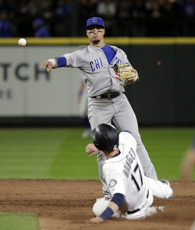 Chicago Cubs shortstop Javier Baez throws to first after forcing out Seattle Mariners' Mitch Haniger at second base during the sixth inning of a baseball game Tuesday, April 30, 2019, in Seattle. Baez completed the double play on Domingo Santana to end the inning. (AP Photo/Elaine Thompson)