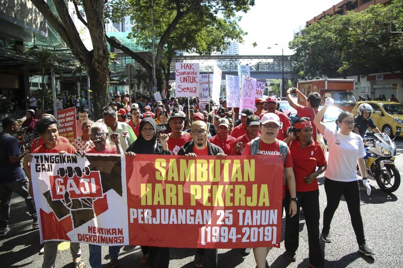 Malaysian workers stage a rally marking May Day in Kuala Lumpur, Malaysia, Wednesday, May 1, 2019. Hundreds of workers demand raise of basic salary and ending towards discrimination. The signs read