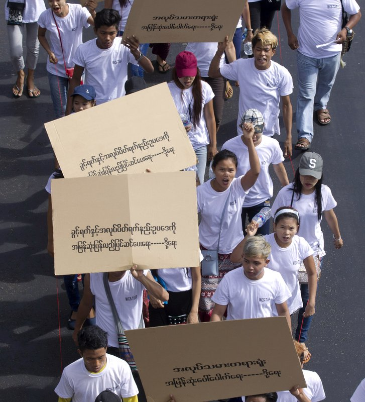 Myanmar labors holding placards read,