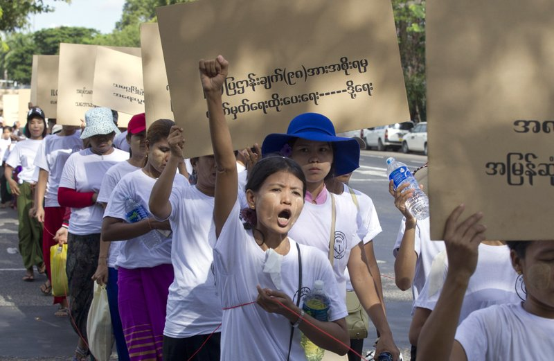 Myanmar workers holding a placard read,